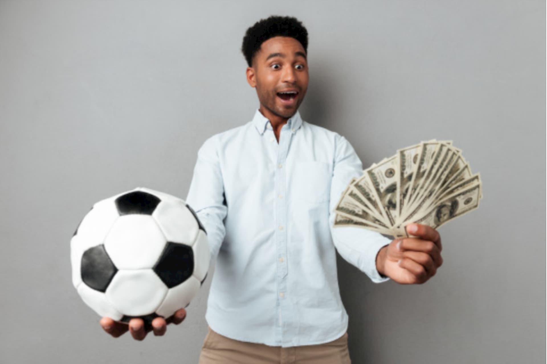 homem segurando um leque de notas e uma bola de futebol após