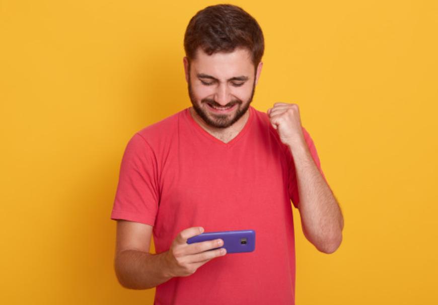 imagem de homem comemorando os resultados de suas apostas olhando seu celular em frente a uma parede laranja