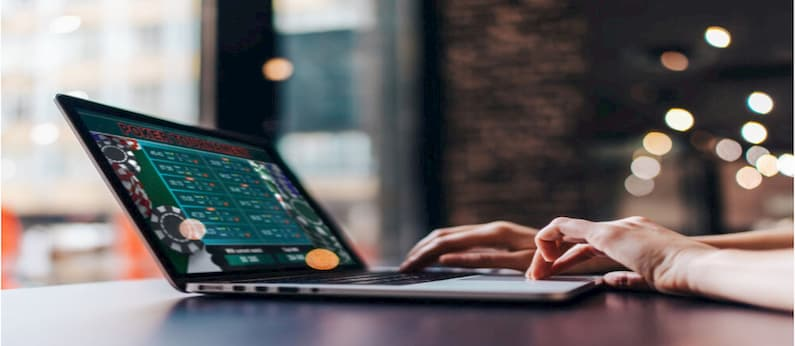 imagem aproximada de pessoa usando laptop para realizar apostas esportivas