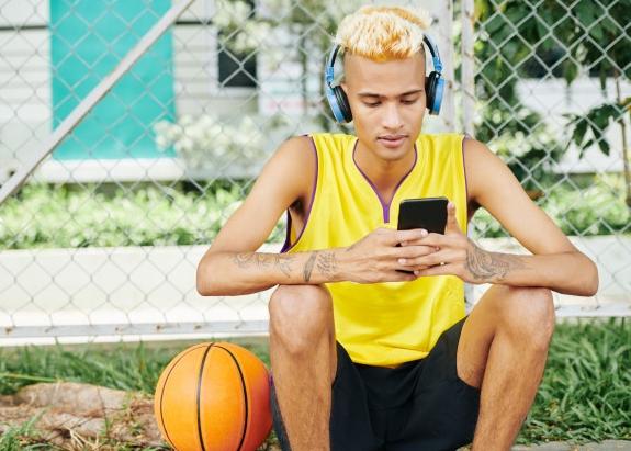 homem loiro com camiseta regata amarela sentado ao lado de uma bola de basquete e mexendo no celular