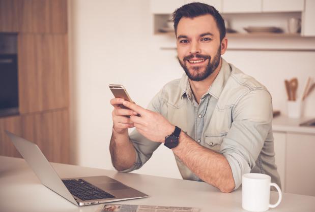 homem de camisa jeans sentado a uma mesa com um laptop usando o celular e sorrindo
