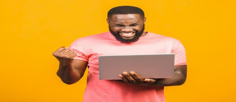homem usando camiseta laranja comemorando segurando um laptop de costas para uma parede amarela
