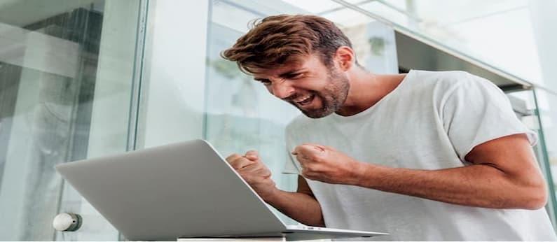 homem de camiseta branca comemora em frente ao seu notebook após lucrar com apostas esportivas