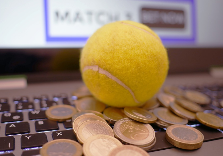 bola de tênis de cor amarela junto de algumas moedas em cima de um teclado de notbook