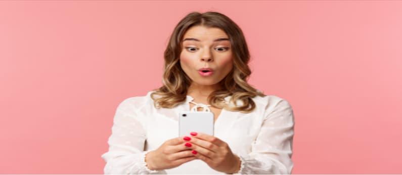 mulher surpresa olhando para o seu celular de costas para um fundo rosa