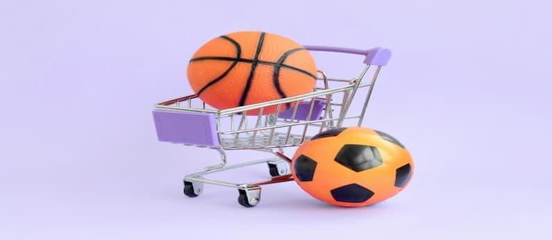 imagem de carrinho de compras com uma bola de basquete laranja dentro e ao lado uma bola de futebol preta e laranja em um fundo roxo