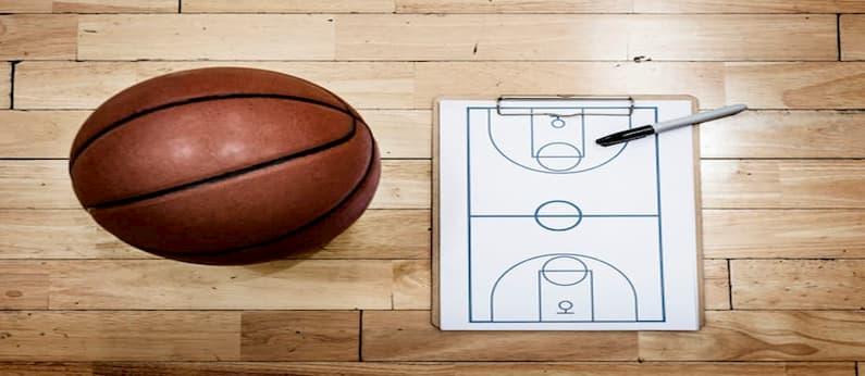 bola de basquete laranja ao lado de um modelo da quadra em preto e branco junto de uma caneta em cima de uma chão de madeira lustrada