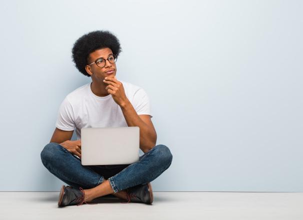 homem de calça jeans e camisa branca sentado no chão de costas para uma parede branca e com um laptop no colo