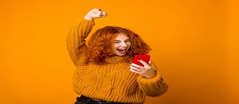 mulher ruiva usando casaco laranja comemora enquanto segura um celular vermelho de costas para uma parede laranja