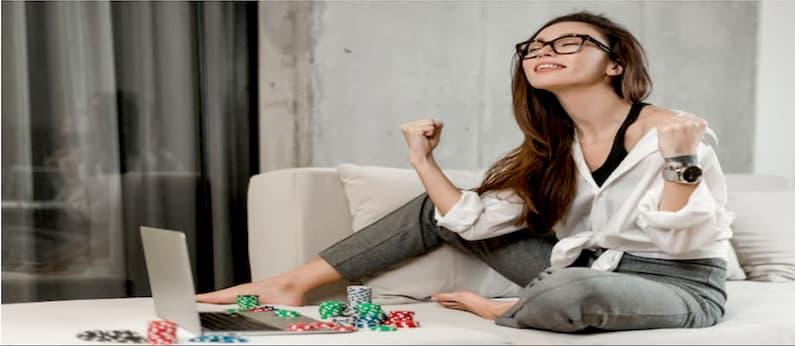 mulher sentada em um sofá cinza de frente para um laptop usando calça cinza e uma camisola branca junto de um par de óculos comemora o resultado de suas apostas