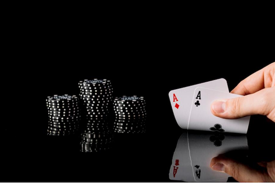 imagem ampliada de uma mão levantando um par de cartas em cima de uma mesa preta com fichas de poker nas cores preta com detalhes brancos