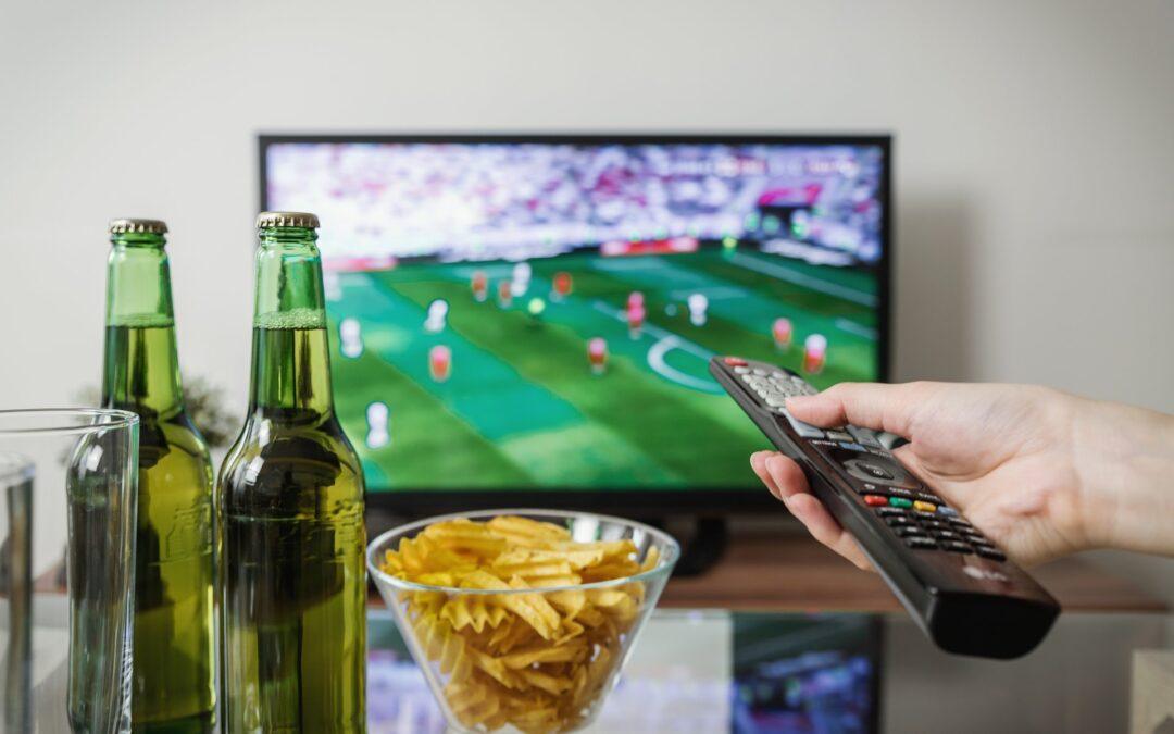 em uma mesa de vidro estão duas garrafas verdes com cerveja e um pote com batatas chips enquanto uma pessoa segura o controle da televisão que está ao fundo