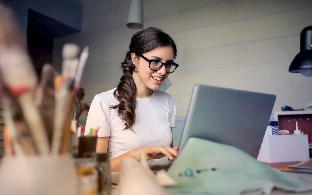 mulher de camiseta branca e óculos sentada a uma mesa com