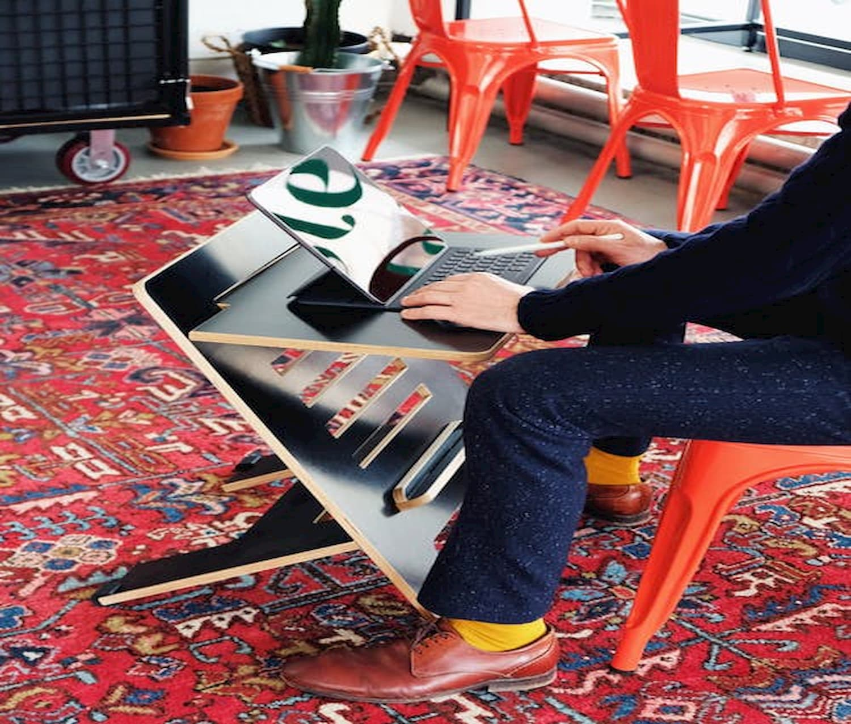 em uma sala com um tapete colorido um homem de sapato marrom e calça e camisa de cor escura está sentado a uma pequena mesa usando um laptop