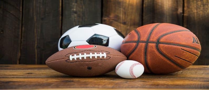 uma mesa de madeira estão bolas de futebol, futebol americano, basquete e beisebol