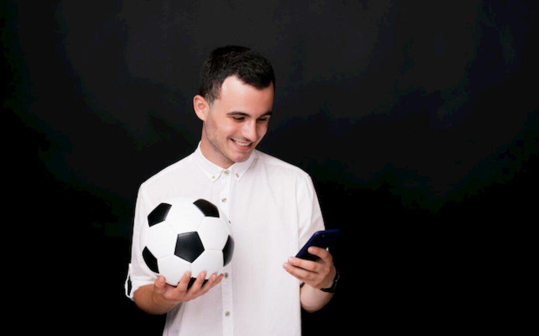 jovem de camisa branca de costas para um fundo preto segura uma bola e sorri olhando para seu celular