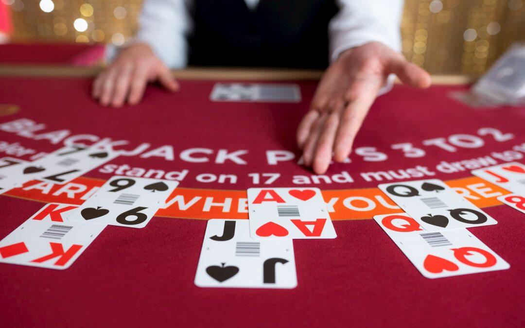 em umesa de casino vermelha estão diversas cartas de um baralho nas cores preta e vermelha