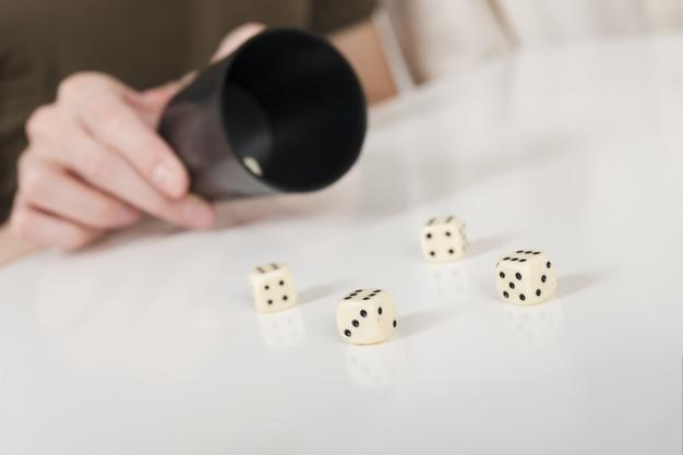 em uma mesa branca uma pessoa joga dados de dentro de um copo preto