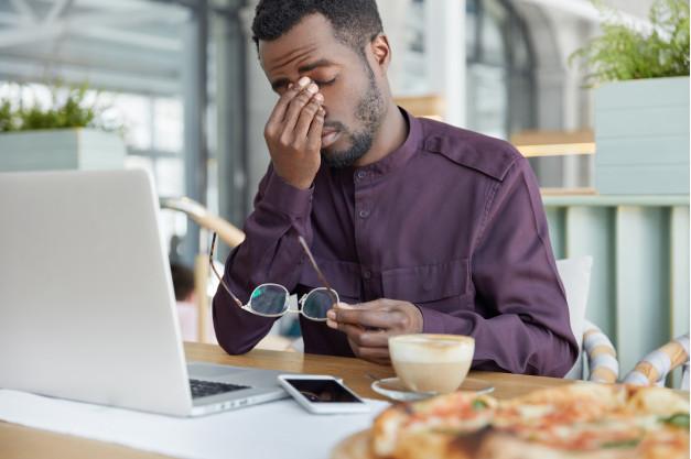 homem vestindo camisa vinho sentado a uma mesa de madeira com um laptop celular e xícara çeva sua mão ao rosto enquanto tira os óculos