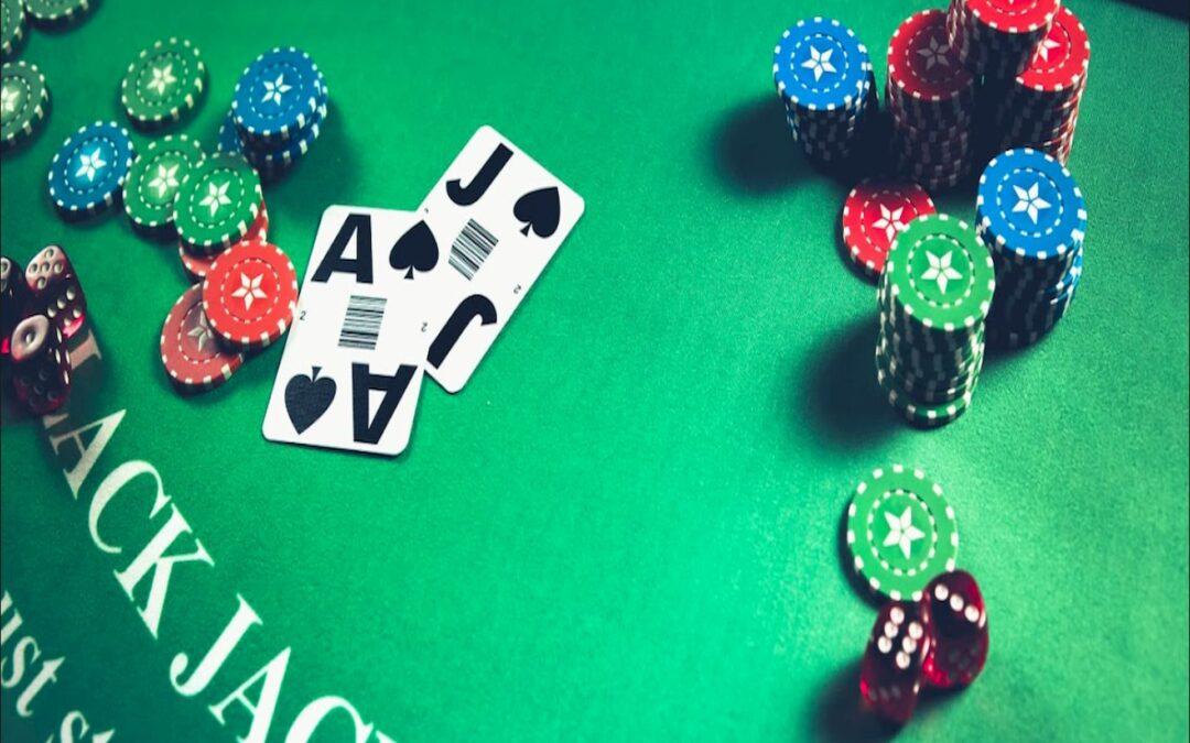 em uma mesa de jogos verdade estão diversas fichas nas cores azul, verde, vermelho e preta e duas cartas de baralho pretas e brancas