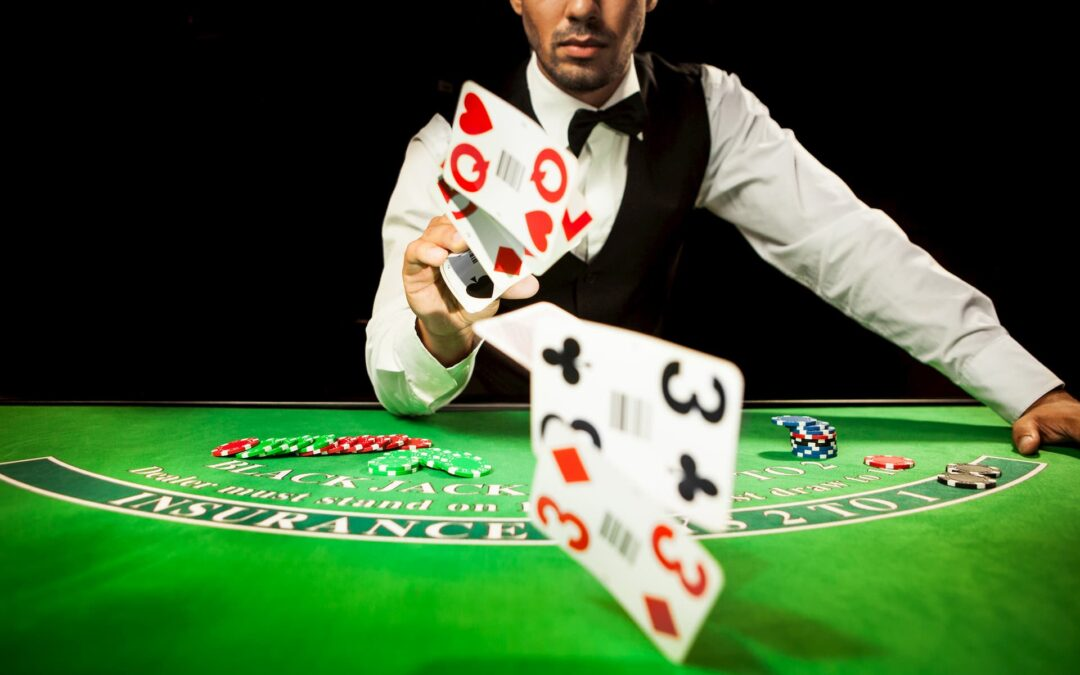 em mesa de cassino na cor verde um dealer usando camisa branca com gravata e colete joga cartas vermelhas e pretas