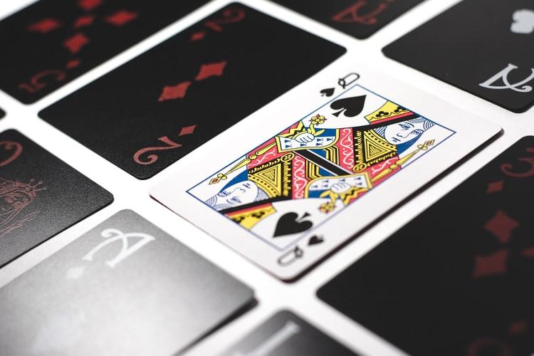 em uma mesa branca estão diversas cartas pretas com número e uma carta com o rei na cor branca