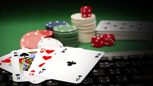 mesa de cassino com maço de cartas ao fundo, seguido por pilhas de fichas e cartas abertas em cima de um teclado preto