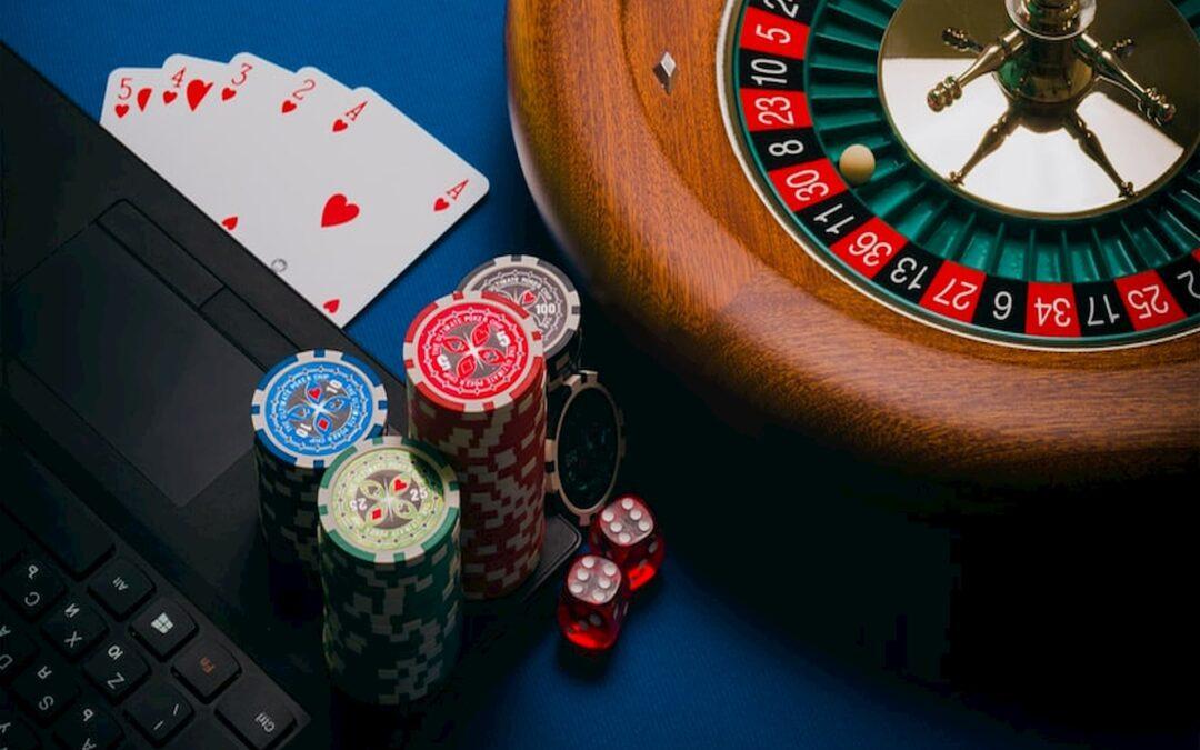 em uma mesa de cassino azul estão um laptop, dados, fichas, um baralho e uma roleta para jogos