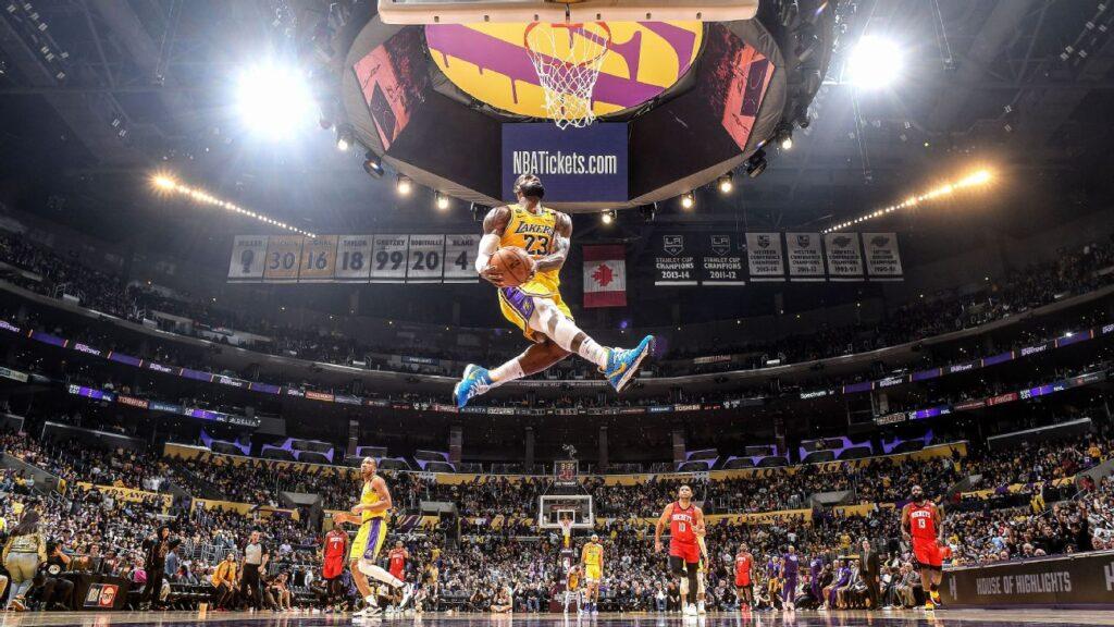imagem panorâmica de Lebron James usando uniforme amarelo e roxo do Lakers se preparando para enterrar bola da cesta durante partida