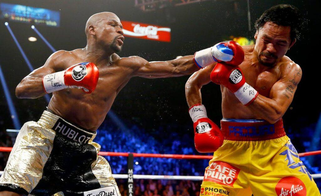 Floyd Mayweather de shorts preto e prateado acerta jab no rosto de Manny Pacquiao durante confronto