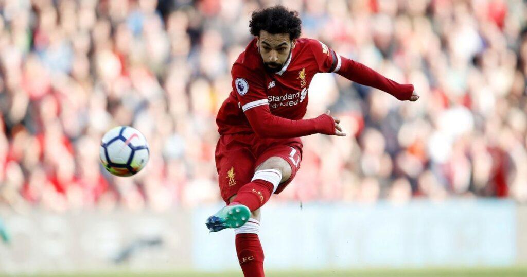 imagem de Mohamed Salah usando o uniforme vermelho do Liverpool chutando bola em direção ao gol durante partida