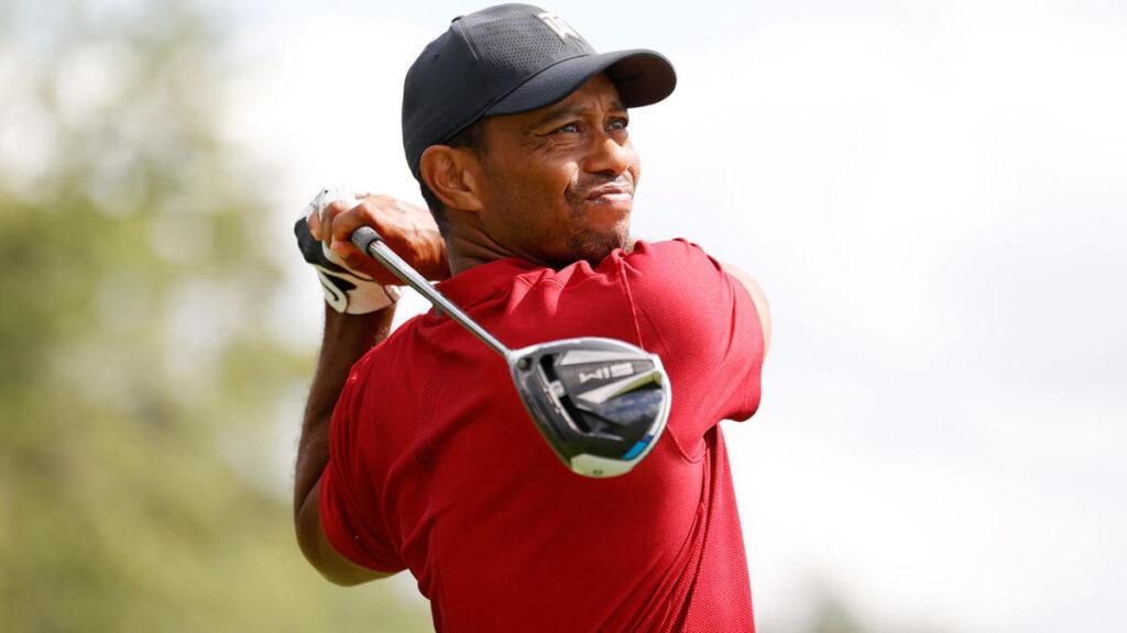 Tiger Woods usando camiseta vermelha e boné preto durante realização de tacada em jogo de golfe