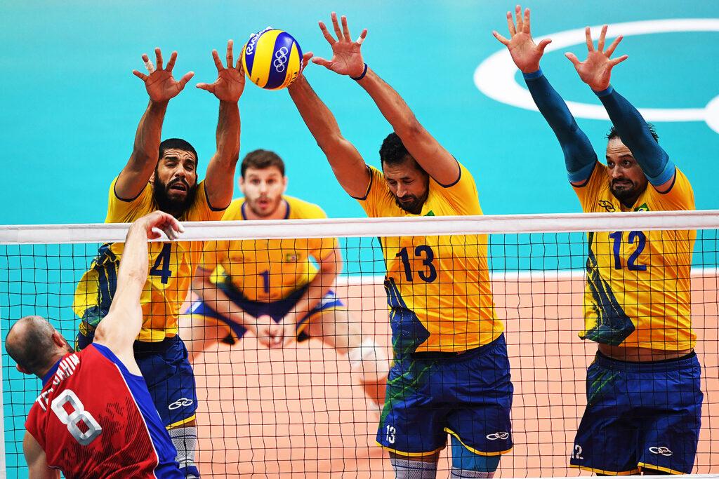 atletas da seleção brasileira de vôlei realizam bloqueio de tentativa de ataque adversário durante partida