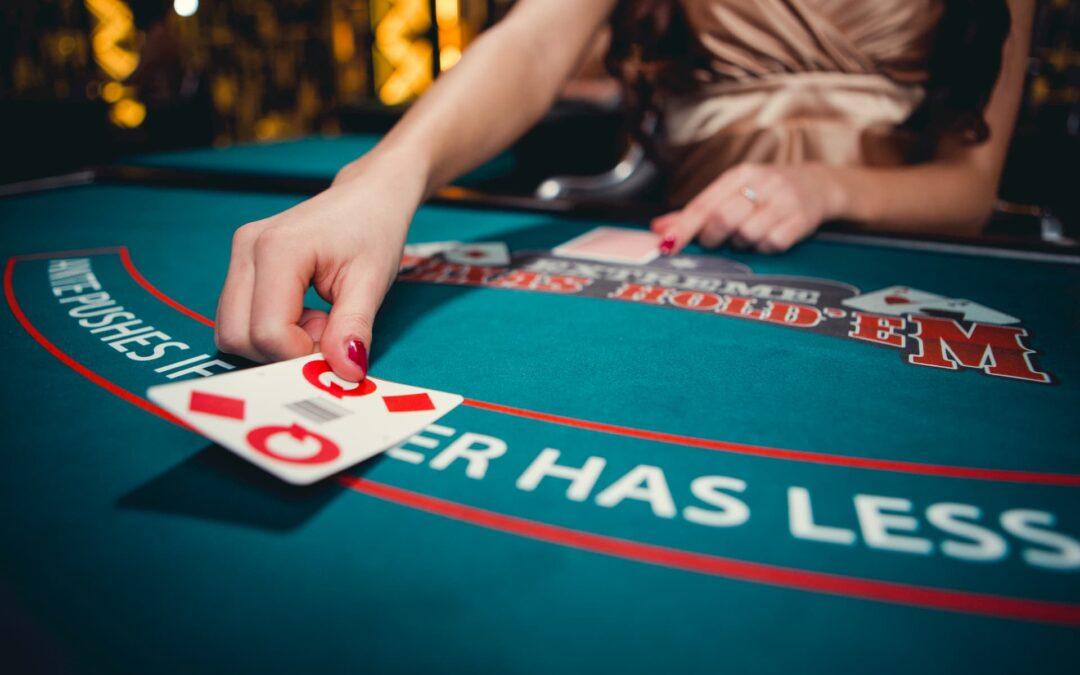 mulher de vestido bronze e unhas vermelhas posiciona carta de baralho em mesa de cassino