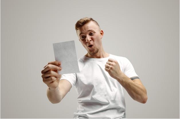 homem de camisa branca comemora enquanto observa o resultado de suas apostas esportivas