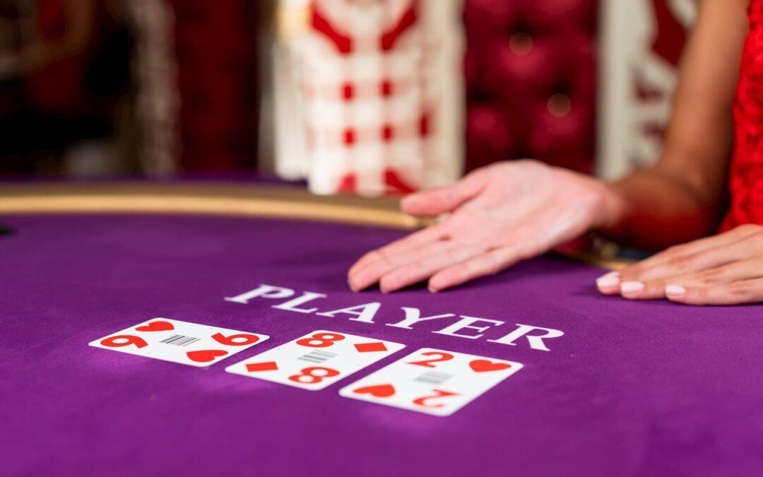 em uma mesa roxa estão três cartas de baralho nas cores branco e vermelho sendo expostas por uma mulher