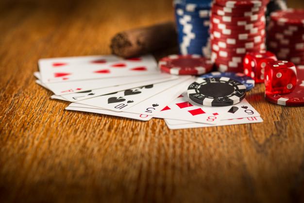 em uma mesa de madeira estão cartas de baralho e fichas de casino nas cores azul e vermelho