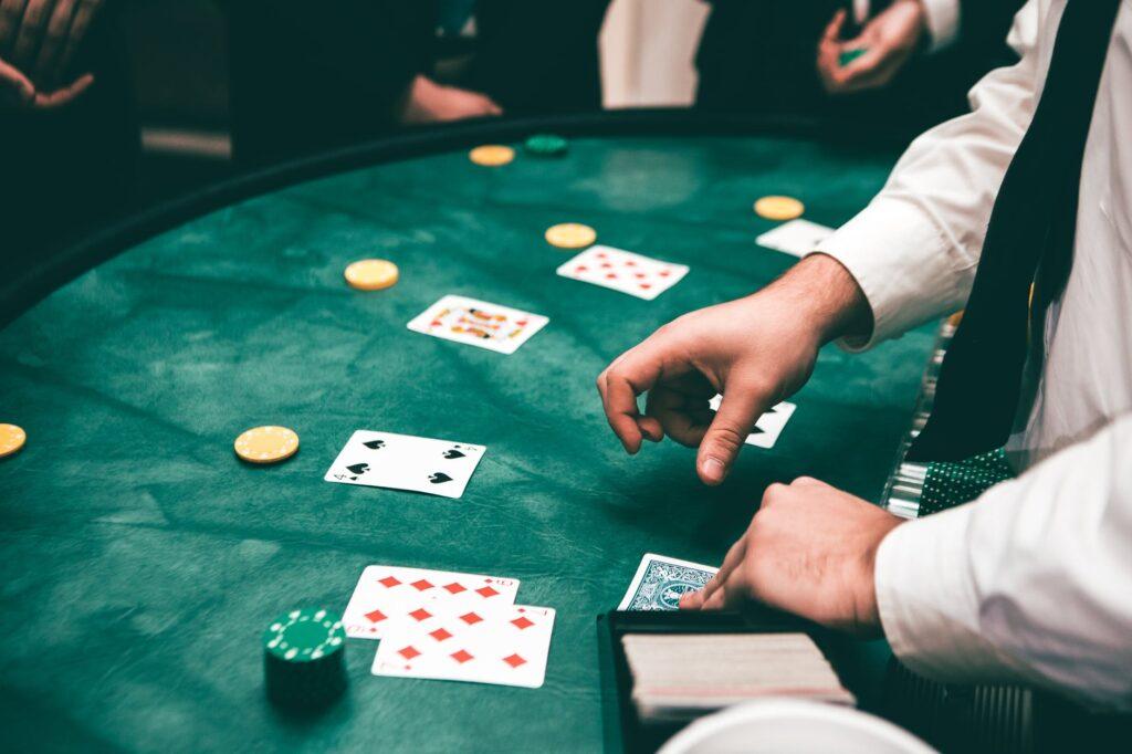 homem de camisa branca e gravata preta distribui cartas e fichas em uma mesa de cassino na cor verde