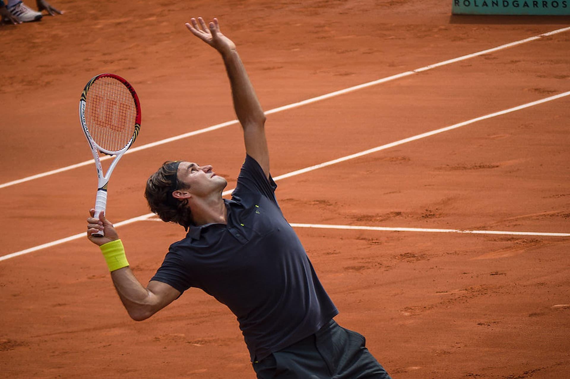 Roger Federer se prepara para realizar um saque durante partida em quadra de saibro