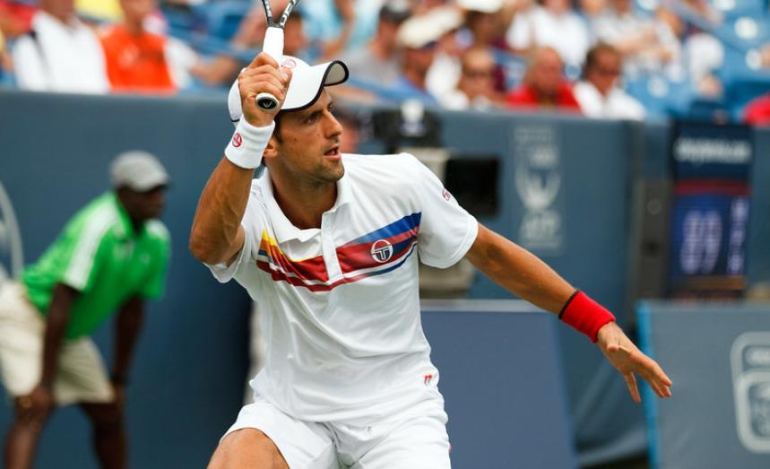 Novak Djokovic rebatendo bola de adversário durante partida de tênis