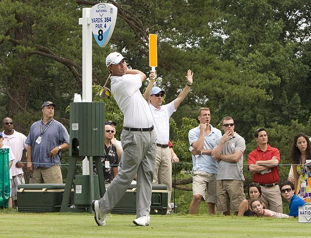 atleta de golfe realizando tacada durante campeonato com público