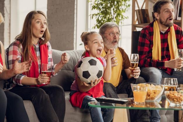 família reunida e sentada em um sofá comemorando resultado de partida