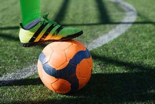 imagem ampliada de um jogador com chuteira verde apoiando o pé em uma bola de futebol laranja e azul