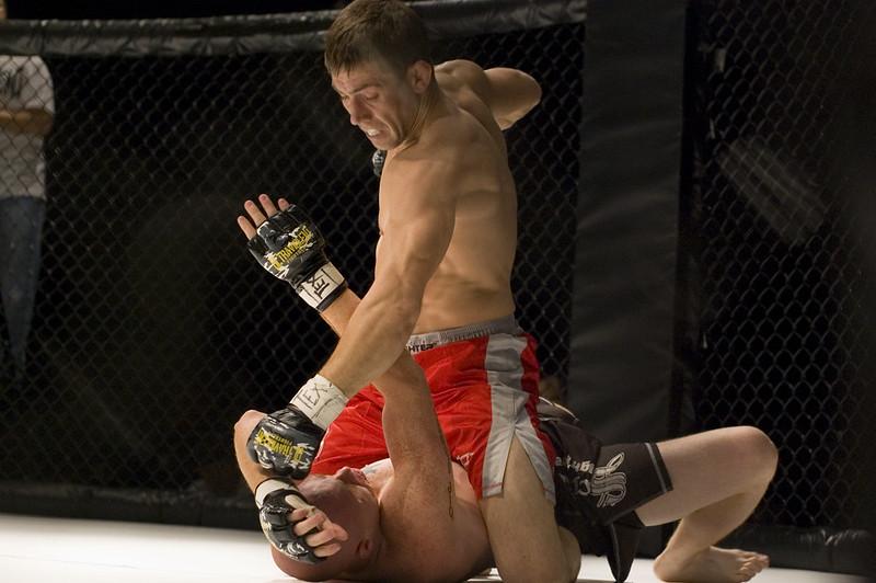 lutador montado em adversário desferindo socos em sua cabeça