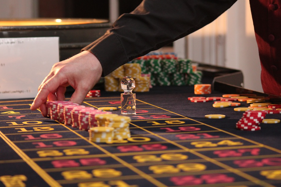 imagem ampliada de um dealer organizando pilhas de fichas de poker em cima de uma mesa