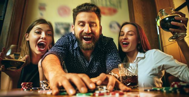 três amigos sorriem e gritam enquanto jogam em cassino