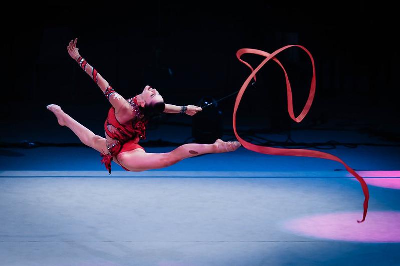 ginasta se apresentando com fita vermelha
