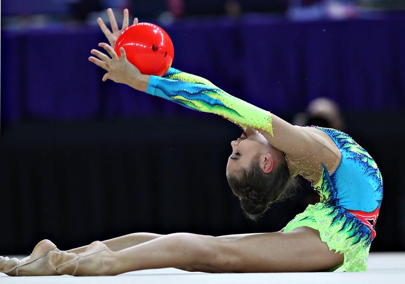 Atleta de ginástica rítmica se apresentando com bola vermelha