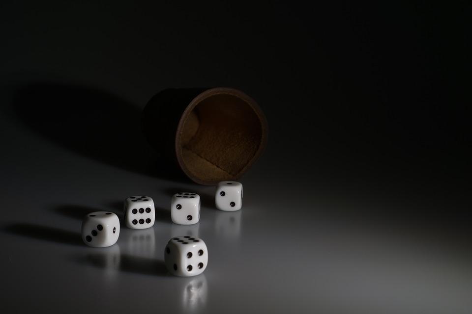 imagem de cinco dados caidos em cima de uma mesa ao lado de um copo de couro