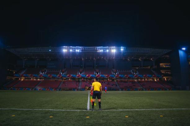 árbitro de amarelo parado no campo de futebol em frente às arquibancadas